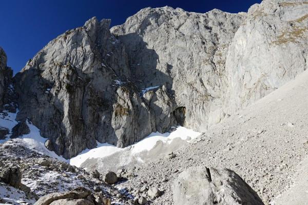 Aus der leicht überhängenden Felswand kommen Wassertropfen herab (zumindest hoffe ich, dass es nur Wasser war :-). Links der Bildmitte das Grimmingtor.