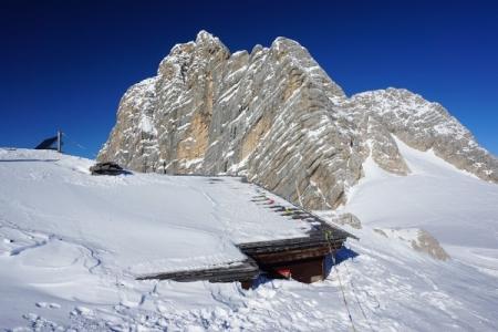 Blick über die eingeschneite Dachsteinwartehütte auf die gefurchte Dachstein-Südwand.