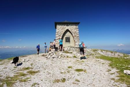 ... hinter dem bereits andere Wanderer vor dem am Gipfelplateau kräftigen Wind Schutz suchen.