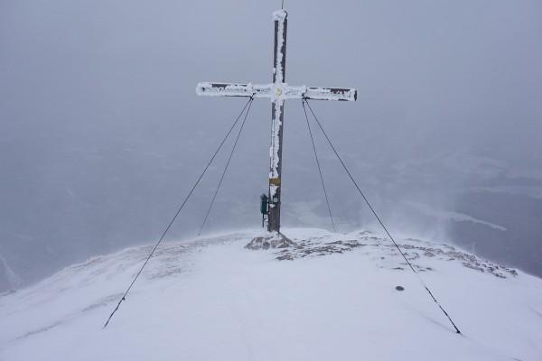 Beim Gipfelkreuz peitscht böiger Wind scharfe Schneekörner ins Gesicht