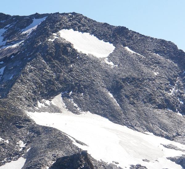 Wanderer beim Queren des Firnfeldes unterhalb des Westrückens, auf dem der Weg auf den Kleinen Ankogel führt (linker Bildbereich).