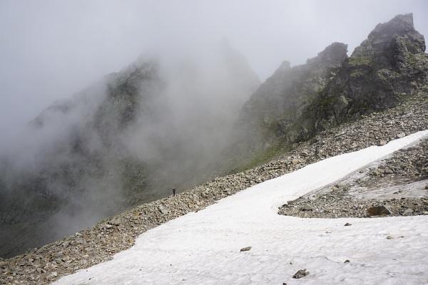 Martin unterhalb des Schneefeldes auf einem Steinwall stehend.