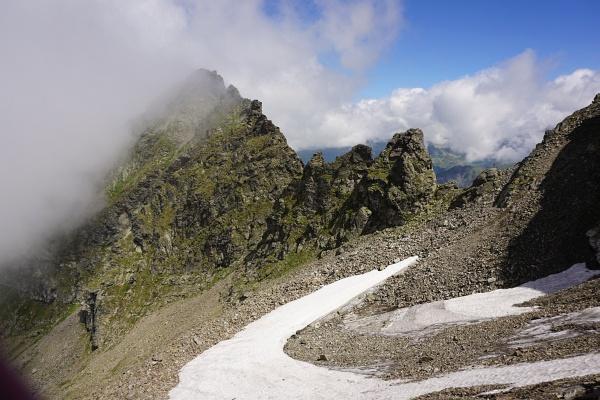 Das Ende des Schneefeld-Bogens zeigt hinauf auf das Gedenkkreuz.
