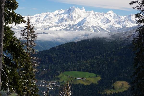 Winterliche Berggipfel (Dachstein) über grünen Tälern.