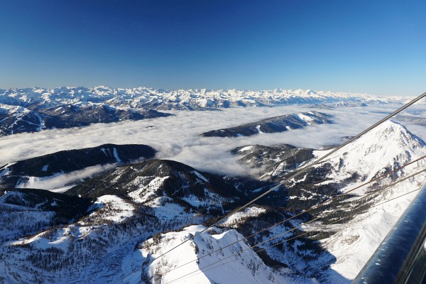 Nebel über dem Ennstal, dahinter die schneebedeckten Gipfel der Niederen und Hohen Tauern.