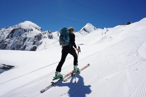 Am Pistenrand zum Alpincenter. Rechts von Ingrid das Kitzsteinhorn.