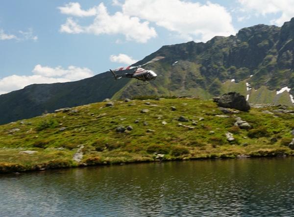 Der Hubschrauber kommt tollkühn über die Geländekante herauf