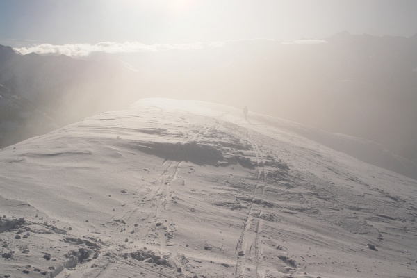 Der Schitourengeher, der kurz nach mir auf den Gipfel gekommen ist, verschwindet bei der Abfahrt in den Wolkenschwaden.