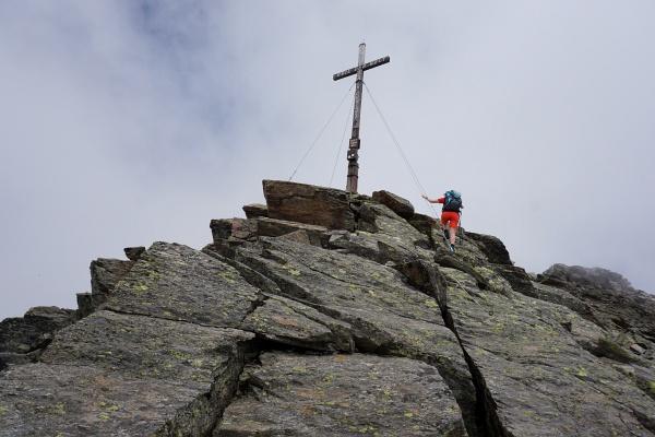 Beim Gipfelkreuz auf der Schleinitz reissen die Wolken kurz auif