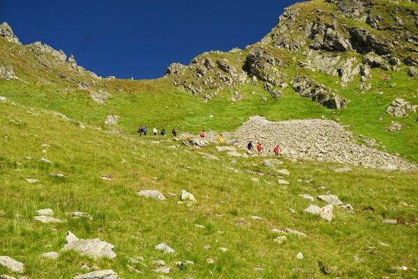 Eine farbenprächtige Wanderergruppe kommt vom Waldhorntörl herab.