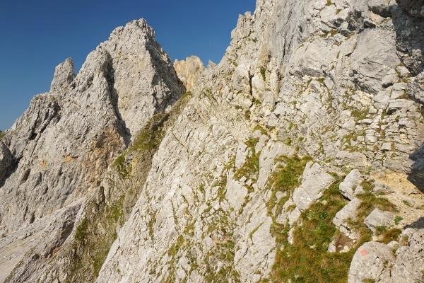 Vom Schotterfeld geht es am Gamsängersteig über ein schmales Steiglein auf Gras- und Felsbändern (von rechts in die Bildmitte).