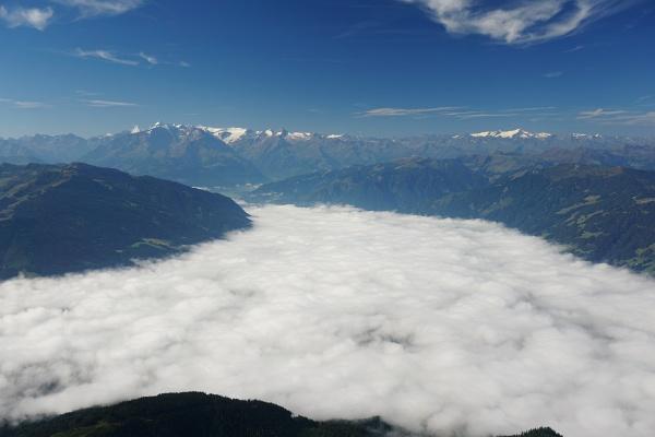 Am frühen Morgen war Saalfelden noch unter der Nebeldecke verborgen. Im Hintergrund die gletscherbedeckten Dreitausender der Hohen Tauern.