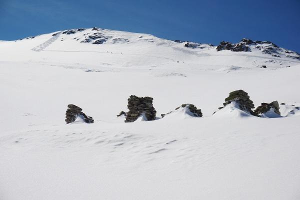 Erzwies - Steinruinen. Im Hintergrund jodeln Skitourengeher bei der Abfahrt vom Gipfel.