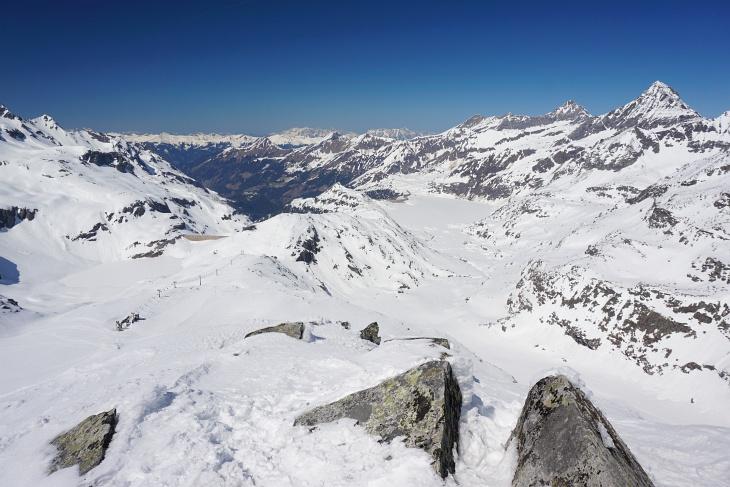 Ausblick vom Medelzkopf zum Weißsee (links mit Staumauer). In Bildmitte folgt das Schigebiet um das Alpinzentrum Rudolfshütte. Rechts hinten erkennt man den Tauernmoossee. Am rechten Bildrand der Hocheiser, links daneben das Kitzsteinhorn.