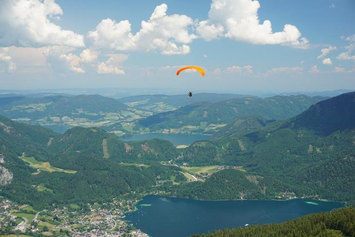 Paragleiterin über St. Gilgen am Wolfgangsee. Im Hintergrund er Mondsee.