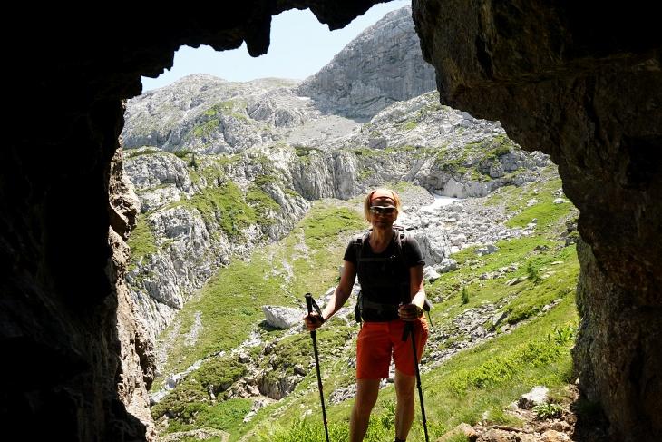 Diese wohl händisch in den Fels geschlagene Höhle könnte ein Kriegsrelikt sein. Im Hintergrund (links) das Abstiegsgelände vom Roßkofel.