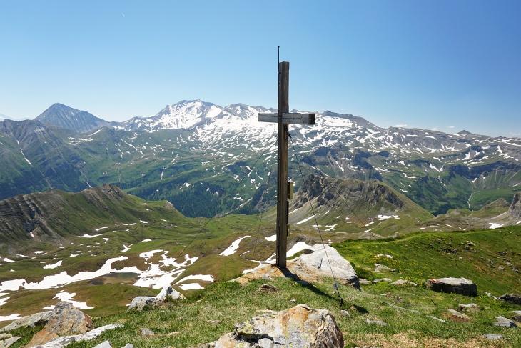Gipfelkreuz am Baumgartlkopf. Hinten der schneebedeckte Hocharn. Ganz links der Ritterkopf.