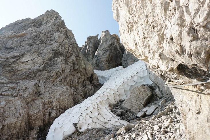 Die Schlucht mit dem Hartschneefeld schaut auf den ersten Blick gar nicht so schlimm aus. Aber links sind die Felsen durch das Schmelzwasser glitschig und rechts liefert kurz darauf eine kleine Steinlawine dem Steinhaufen Nachschub.