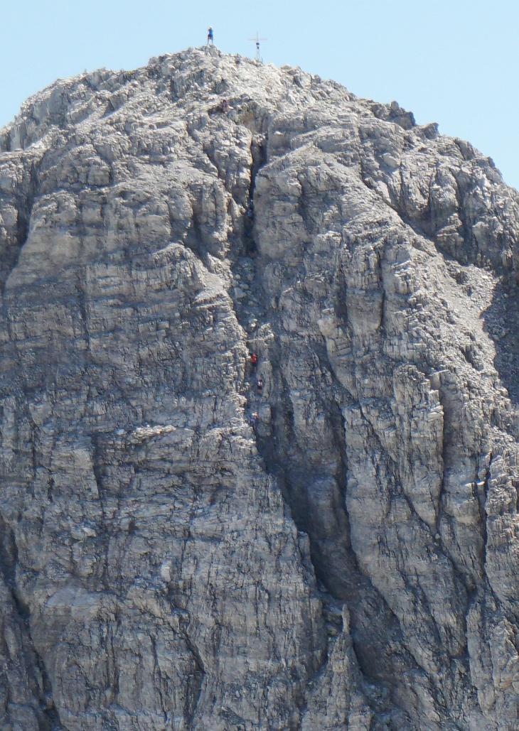 Wenn wir schon bei Zoomblicken sind: Im Kamin kamen gerade 5 weitere Bergsteiger herunter. 3 in Bildmitte und 2 weiter oben im Bereich der dunklen Engstelle.
