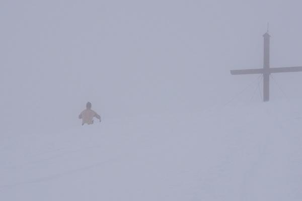 Beim Gipfelkreuz am Pleschnitzzinken. Harte Burschen ziehen sich auch im peitschenden Wind um.