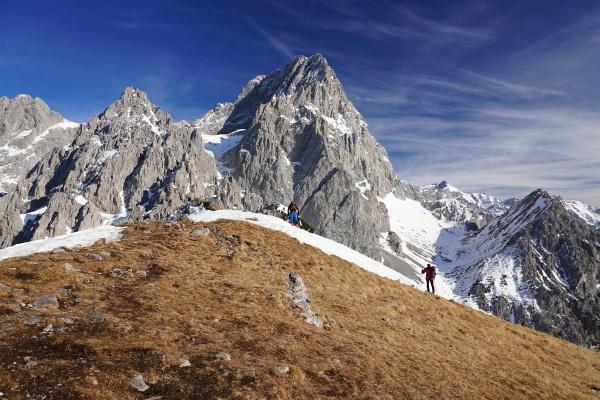Einige Skitourengeher warten im Angesicht des dominanten Torstein auf den richtigen Auffirn-Zeitpunkt im Steilhang.