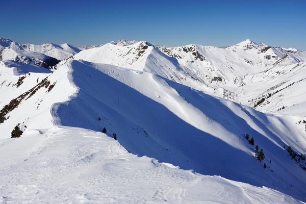 Abgefahren wird über einen Vorgipfel - ebenfalls mit Gipfelkreuz - im Steilhang beim Übergang vom Schatten zur Sonne