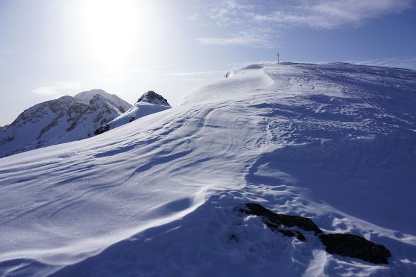 Das Gipfelkreuz am Karlspitz ist in Sicht. Im obersten Abschnitt ist es abwechselnd windgepresst oder hartgefroren.