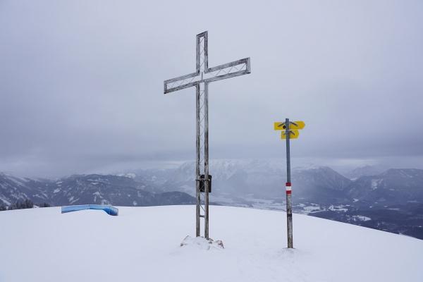 Eingeschränkter Ausblick vom Kampl-Gipfelkreuz über Bad Mitterndorf zum wolkenverhangenen Grimming.