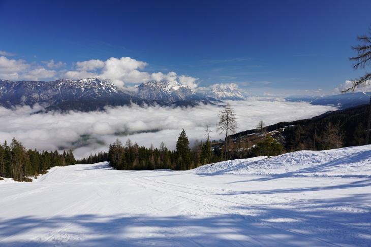 Nebel über dem Ennstal, darüber perfekte, nahezu unberührte Skipisten